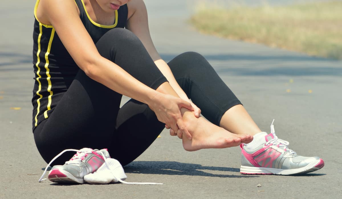 Athletic woman sitting on the ground with ankle pain